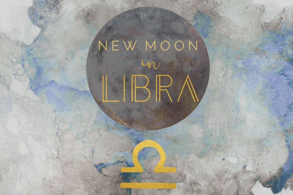 The words New Moon in Libra are written in gold over a dark circle and above a golden astrological symbol of Libra. The background of the image is a blue and gray abstract watercolor.